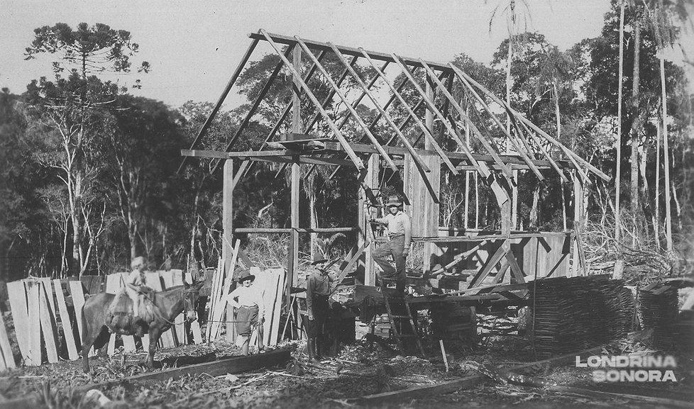 Criança montada em um cavalo, olhando para o esqueleto de uma casa em construção. Mulher sentada, homem em pé e homem em cima de uma escada.
