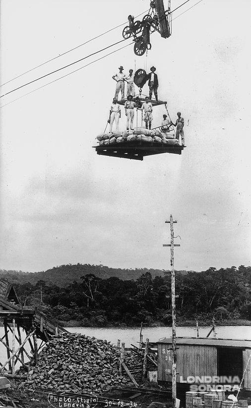 Oito pessoas em uma estrutura de madeira sustentada por um fio, a alguns metros de altura
