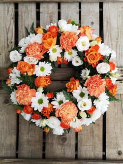 orange and white funeral wreathAshleigh