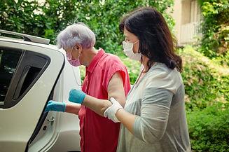 An attentive caregiver helps her elderly