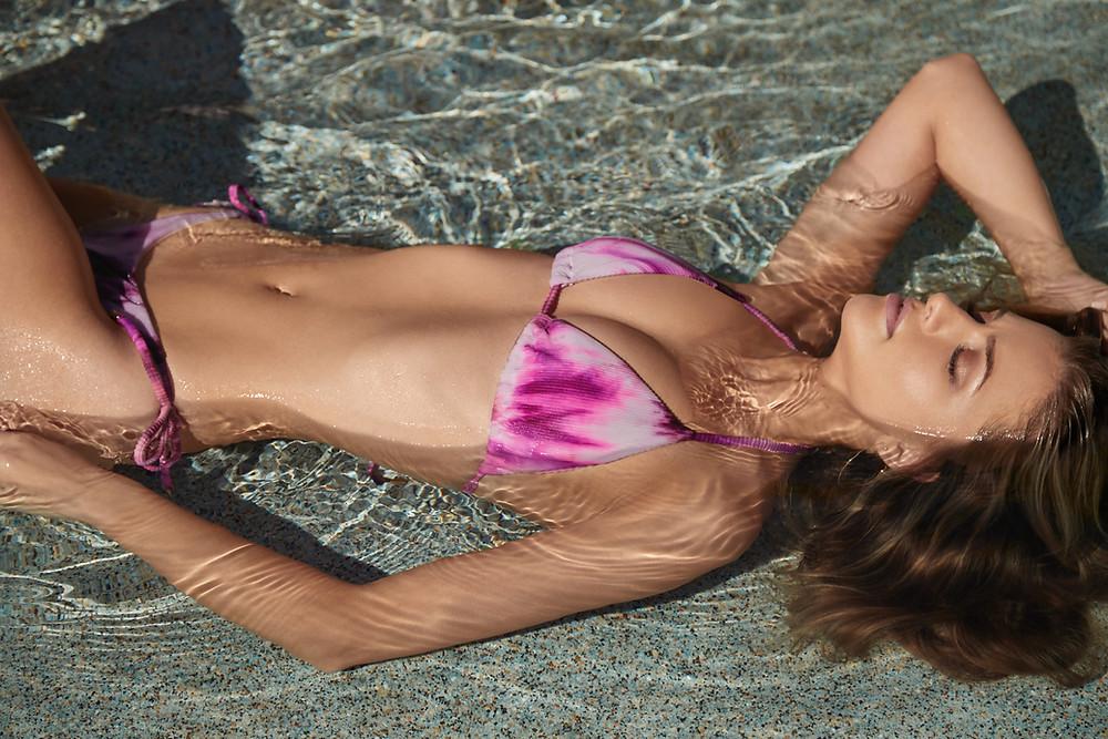 A woman lounging poolside wearing a luxury designer tie dye bikini which she bought online from designer swimwear store sun vixen swimwear located in Canada