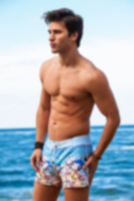 A water sports loving man wearing a printed shorts on a Warm ocean waves in a sunny destination make a perfect pairing with new designer swimsuit from sun vixen swimwear