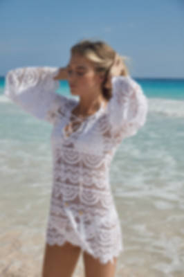 a fashionable women from ottawa canada travelled to an exotic beach holiday is wearing a pliyq white bikini coverup which she purchased online from sun vixen swimwear