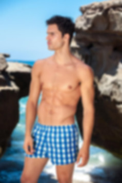 a man from toronto on vacation wearing blue swim shorts he bought from sun vixen swimwear online store