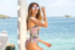 a woman from Barrie Ontario on the beach wearing a one piece swimsuit and sunglasses she bought from sun vixen swimwear online