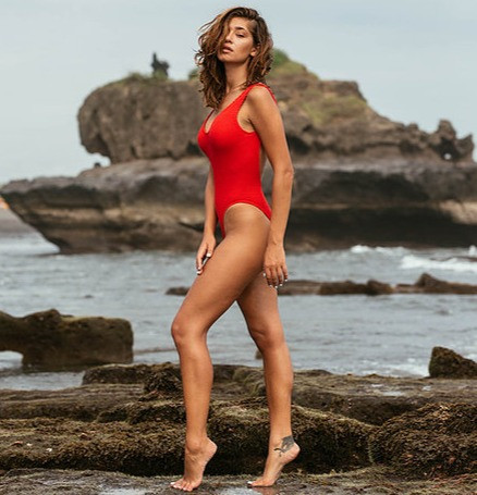 woman wearing a baywatch red one piece swimsuits that is popularly worn in movies by celebrities which she shopped online from sun vixen swimwear that sells best one piece swimsuits online in canada and USA