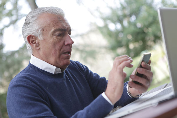 man-in-blue-sweater-holding-smartphone