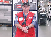 Hubert a Vocational Services Program member standing by a sign at his job at Floor and Decor