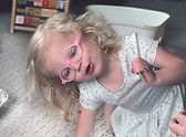 Greta, a toddler with blonde curls and pink glasses wearing a white dress works on a puzzle