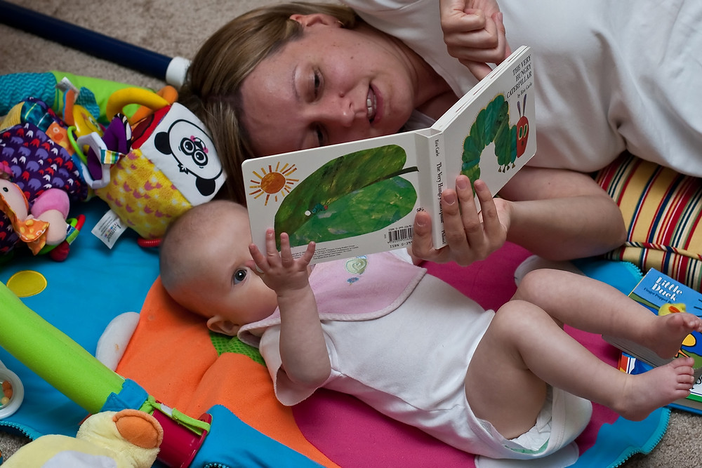 A baby wearing a white onsie and pink bib lays on a colorful mat surrounded by toys. A woman with blond hair and a white tshirt lays next to the baby as they both hold The Very Hungry Caterpillar book. Woman is pointing to a page.