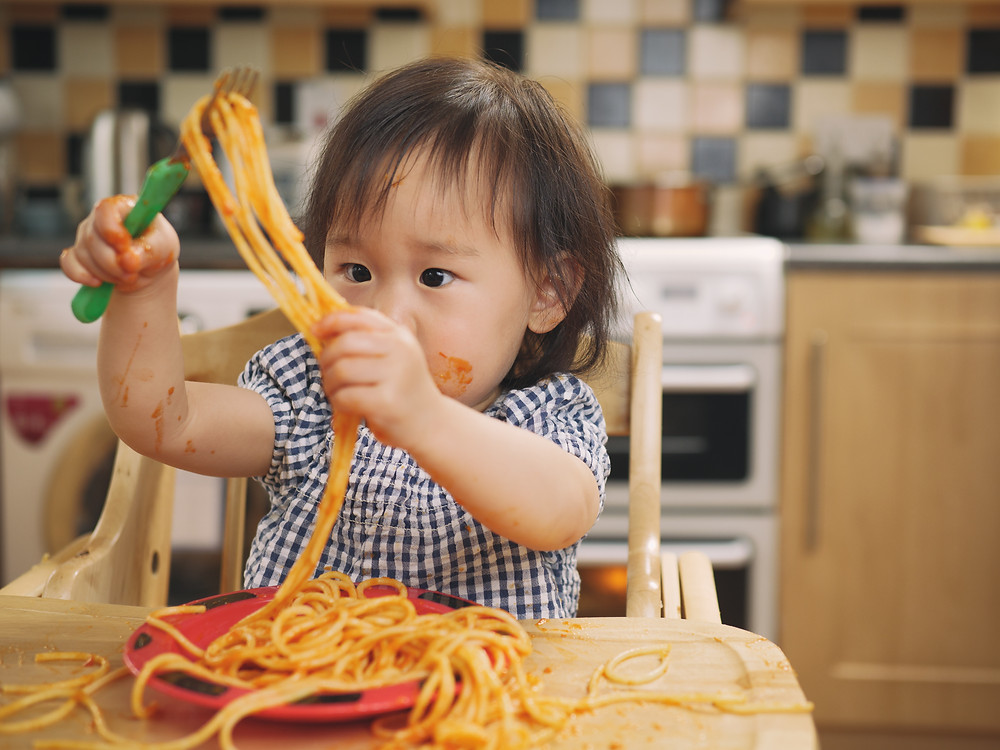 Toddler in black checkered top and spaghetti sauce on her cheek and arm holds a green handled fork in her right hand while pulling spaghetti noodls off the fork with her left hand.