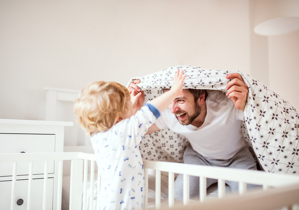 A male with a brown beard wearing a white tshirt and grey sweatpants smiles while covering his head with a comforter. Young todler with blonde curly hair stands in a crib facing the male with his hands in the air.