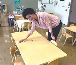 Bailey, a Vocational Services program member cleans a table at Hand and Hand in Oak Harbor.