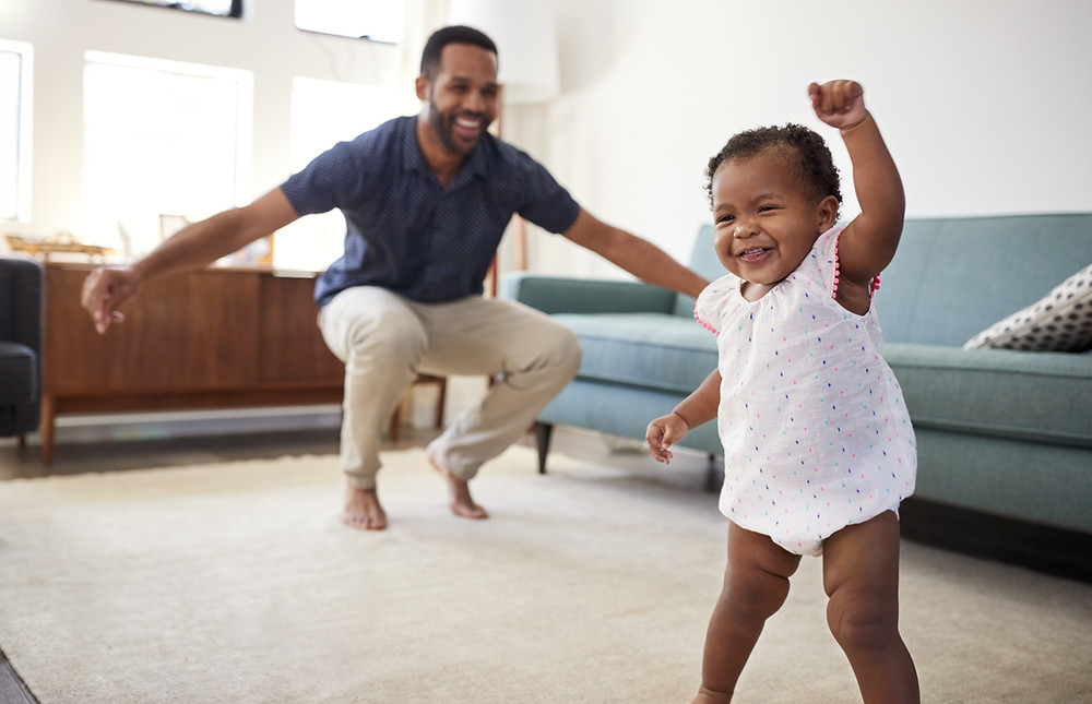 Man kneeling and snapping smiles at small child wearing a flower onsie who both appear to be dancing in a living room in front of a couch.