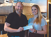 Owner of Bruno's PIzzeria Taylor presents Sherwood employee Corrie a donation check