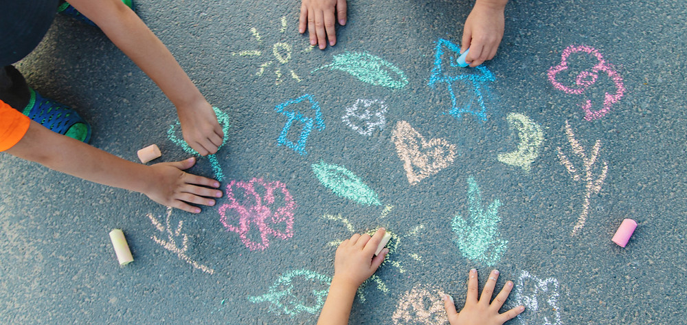 3 young children drawing with sidewalk chalk.