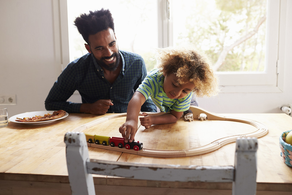 A man and child play with a vintage wooden train set on top of a dining room table.