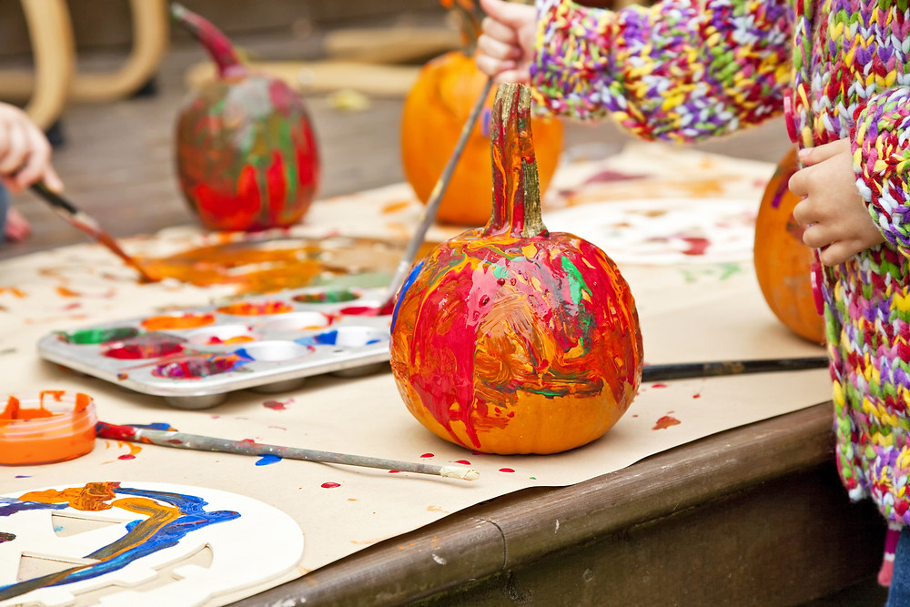 A child paints a pumpkin at a table with other painted pumpkins, paintbrushes and pant pallettes.