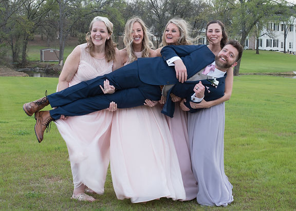 bridesmaids laughing while holding groom