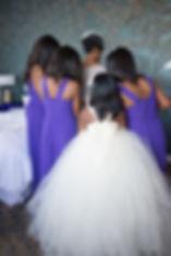bridesmaids buttoning brides dress