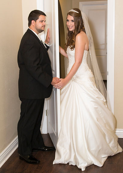bride at groom holding hands behind door at The Castle at Rockwallg
