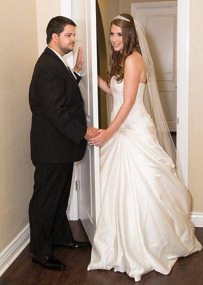 bride at groom holding hands behind door at The Castle at Rockwallg