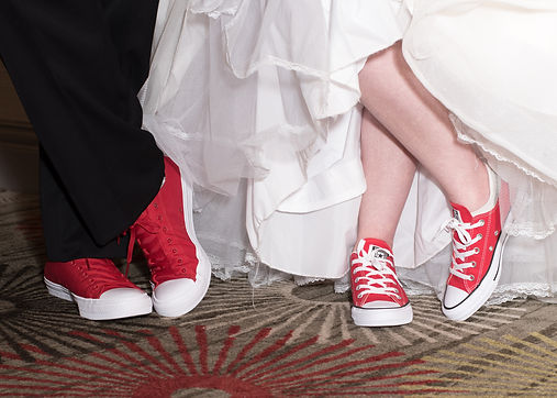 bride and groom wearing converse shoes at wedding reception