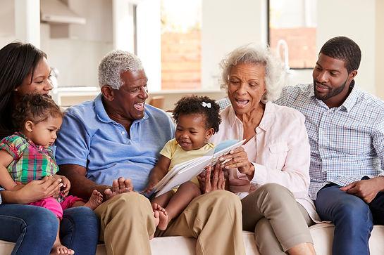 multi-generation-family-sitting-on-sofa-