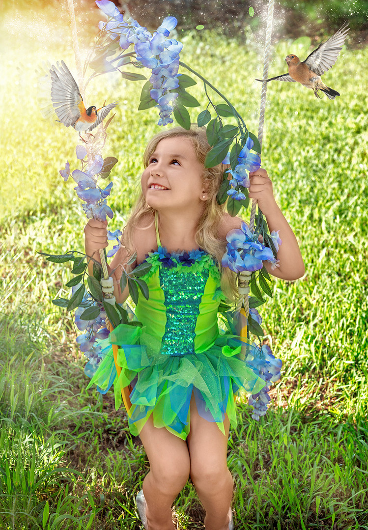 Fine Art children portraits with photo manipulation. Young girl on a sqing with flowers and birds.
