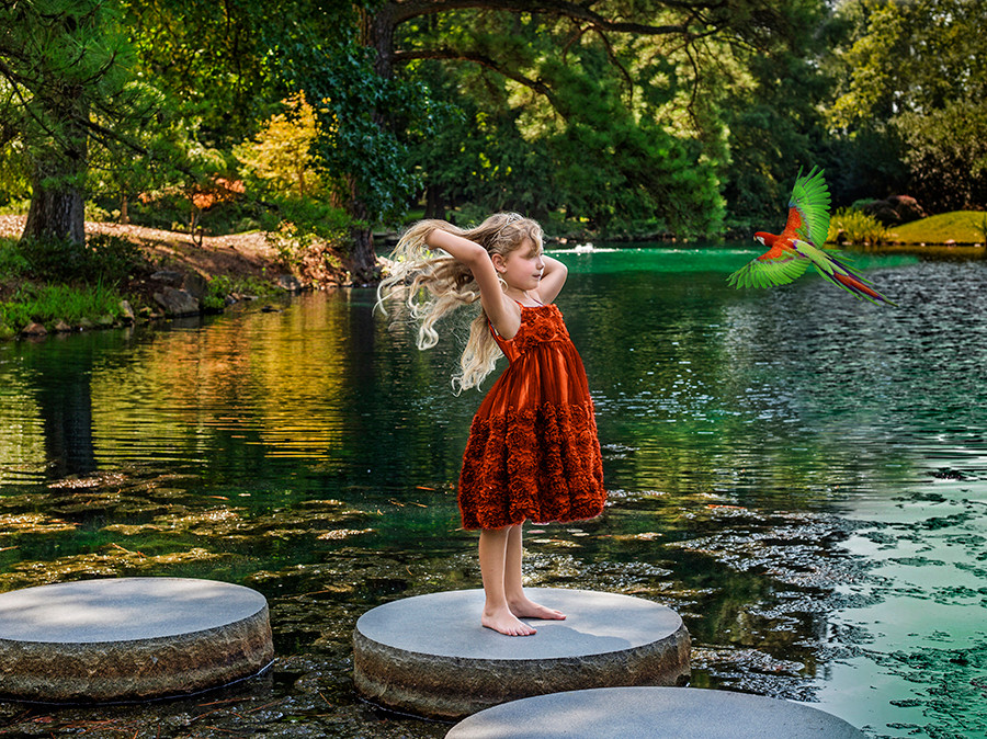 Fine Art children portraits with photo manipulation and compositing. Little girl on a lake with a parrot.