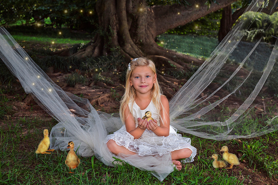 Fine Art children portraits with photo manipulation and compositing. A little girl with ducklings.