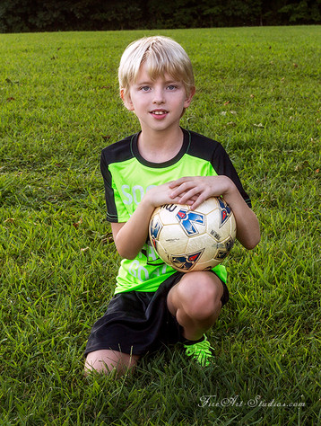 Children photography. Sport outdoor shoot. The boy with a soccer ball.