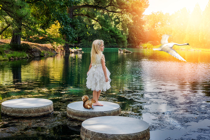 Fine Art children portraits. A little girl with a squirrel and a bird on a lake.