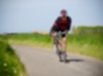 Man on road bike riding down open countr