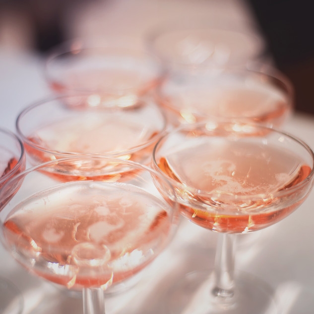 group of glasses with pink champagne on