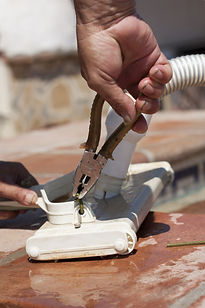 man repairing a pool cleaner with a tool