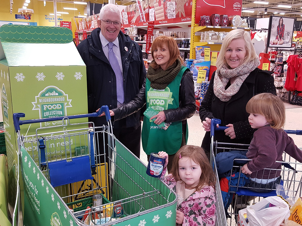 Stewart Dickson MLA and Jill McIlreany (Carrick Foodbank) with Caroline Rafferty and her children Archie and Lacey who is making the family contribution to the Foodbank