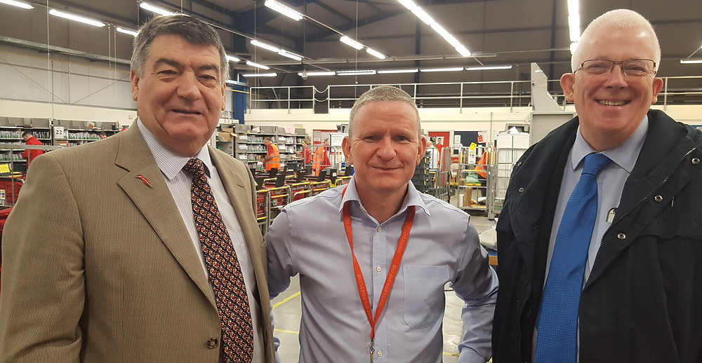 Alliance's Noel Williams (left)  Stewart Dickson MLA (right) with Royal Mail Area Manager Davy Hamill at the Carrickfergus Sorting Office