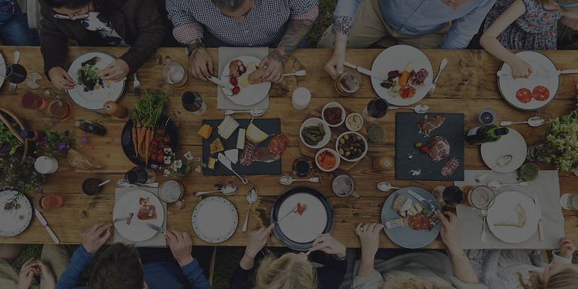 overhead view of a dining table full of food, plates, and people enjoying a meal together