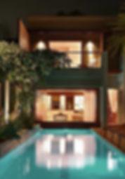 vue de nuit sur une villa luxe de deux niveaux avec piscine bois à Bali par TNT Architecture