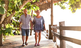 Happy senior couple walking holding hand at Koh Phangan beach promenade - Active elderly a