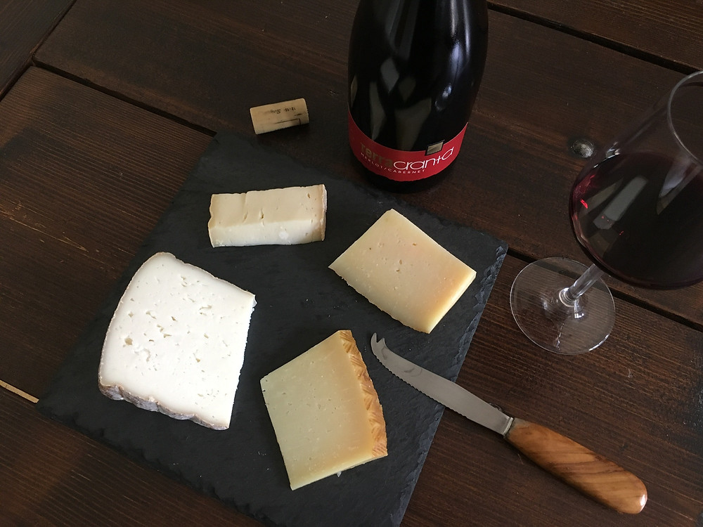 Bottle with a glass of red wine and a cheese platter