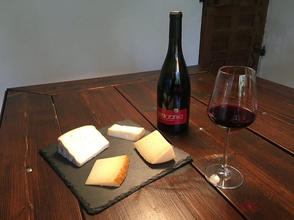Bottle with a glass of red wine and cheese platter