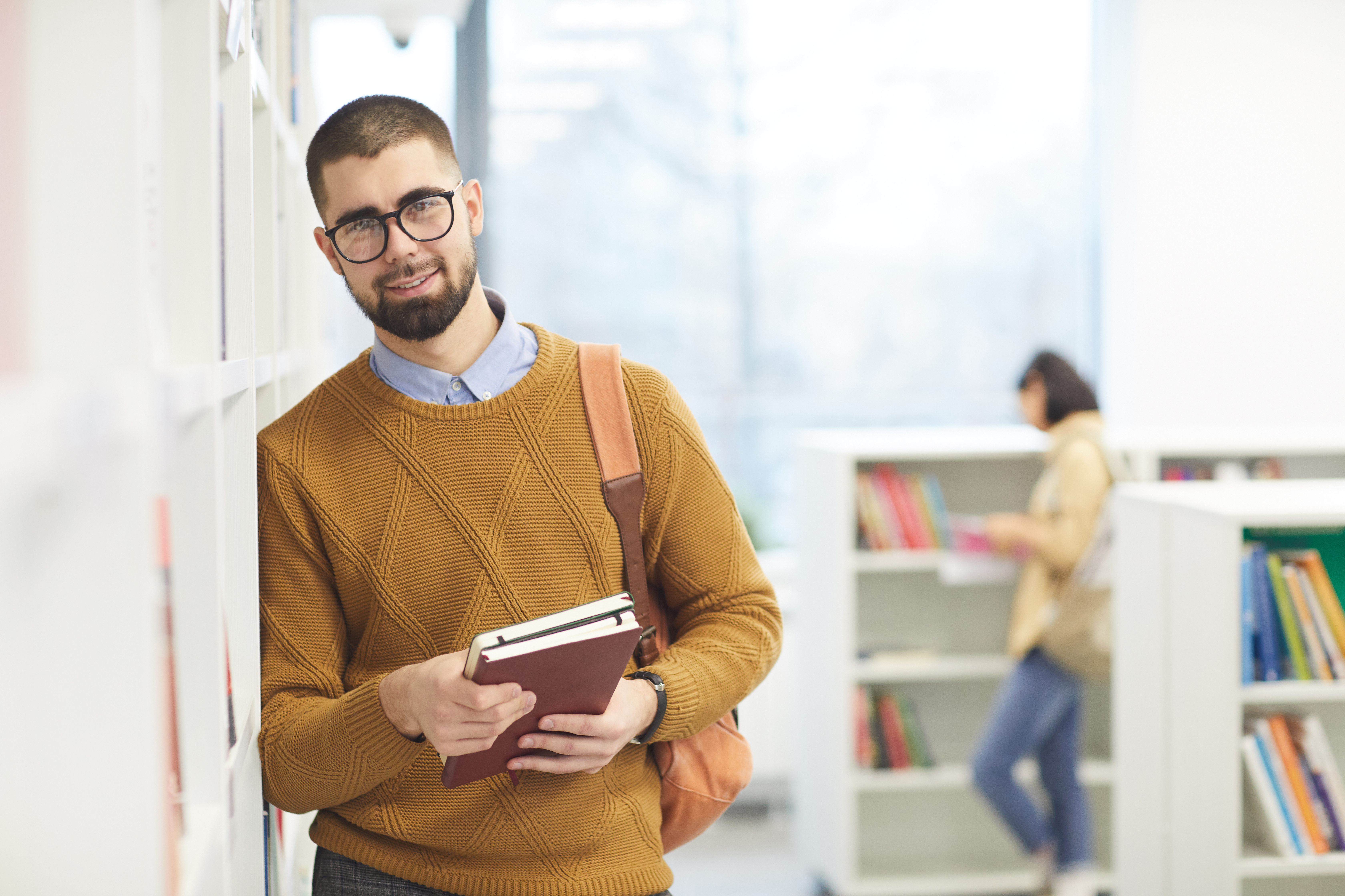 smiling-adult-student-posing-in-library-