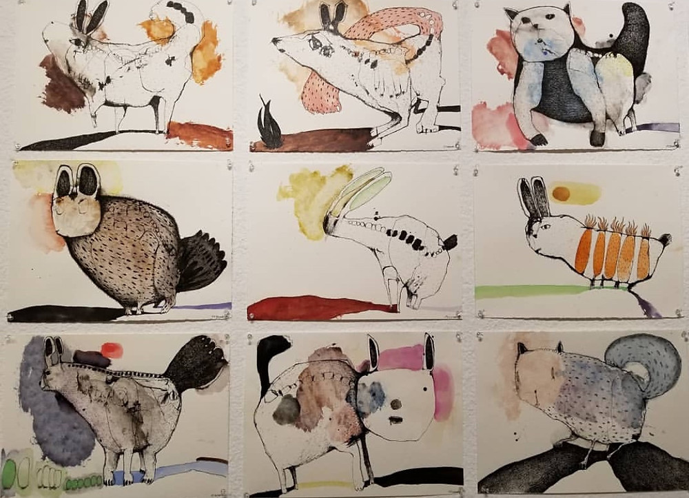installation photo of nine ink and watercolor drawings of unusual mounted to the wall, unframed,