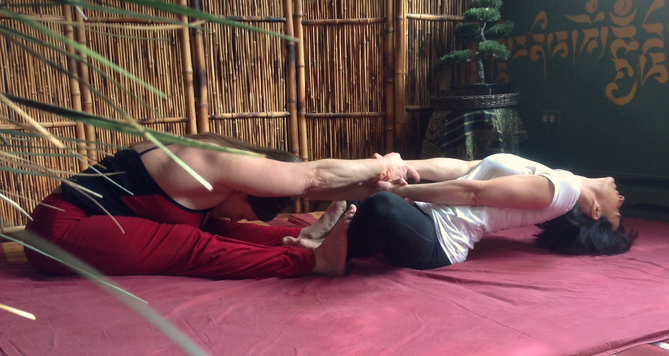 tess and a client doing a partner yoga posture called sea saw