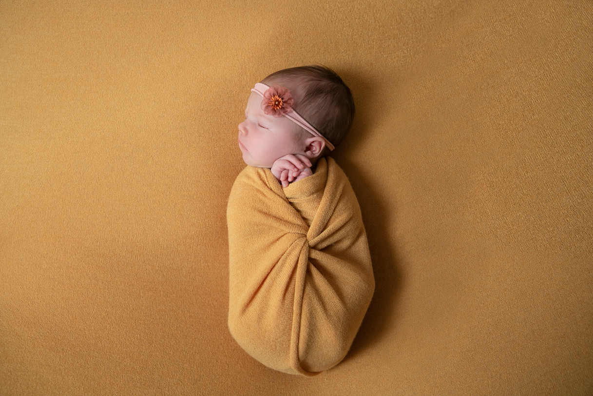 Baby girl in yellow mustard wrap and backdrop