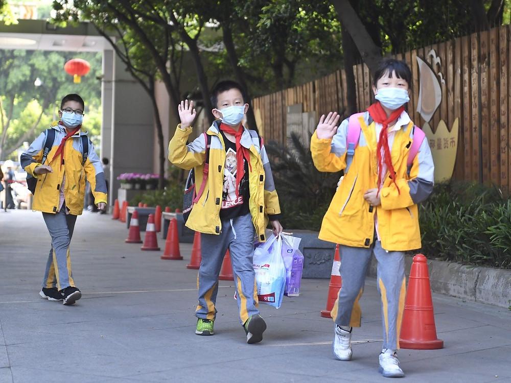 três crianças chinesas chegando na escola