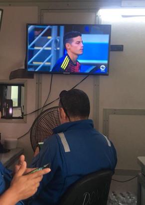 Funcionarios en un contenedor destinado como cuarto de bombas viendo el partido de la selección Colombia contra Polonia en el mundial de fútbol Rusia 2018. Campo petrolero en el municipio de La loma, departamento del Cesar, Colombia. 2018