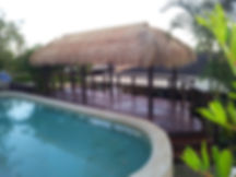 Brisbane Thatched Balinese Hut And Deck next to pool.